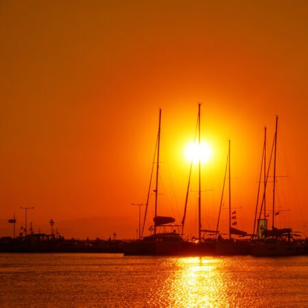 Silhouettes of yachts with tall masts at sunset at the port of Aegina, Saronic Islands, Greece 写真素材