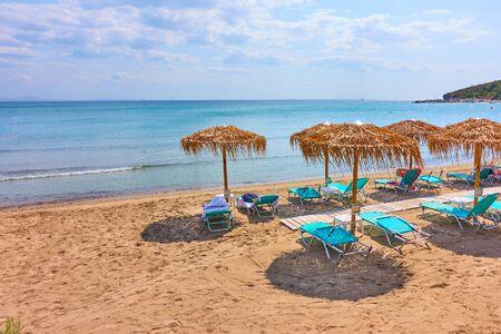 Beach with straw umbrellas by the sea on sunny summer day, Agia Marina, Aegina Island, Greece - Greek resort