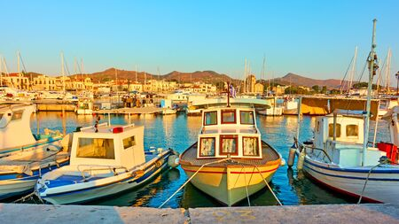Fshing boats in the port of Aegina town at sunset, Greece - Panoramic view