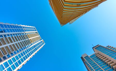 Angle shot of modern many-storied apartment buildings against the clear blue sky