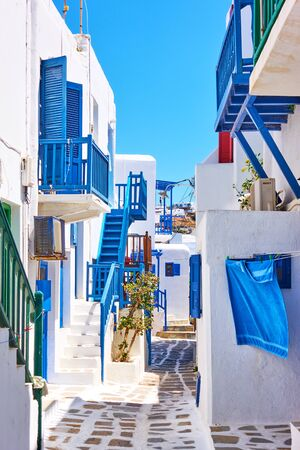 Street with white small houses with blue balconies in Mykonos island, Greece. Greek cityscape 版權商用圖片