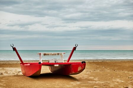 Red safety boat - catamaran by the sea on the beach in Rimini, Italy - Seascape
