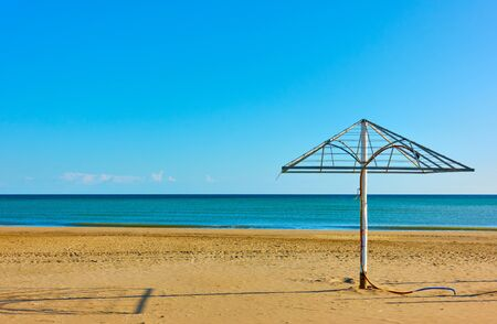 Sandy beach with old parasol in Rimini on the shore of the Adriatic sea, Italy - Minimalistic seascape 版權商用圖片