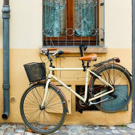 Old bicycle with basket parked near home, Rimini, Italy