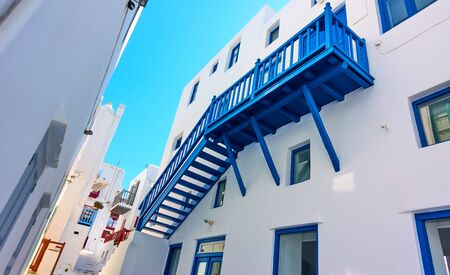 Perspective of old street with whitewashed houses in Mykonos island, Chora town, Greece. Wide angle shot