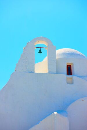 Dome and belfry of Church of Panagia Paraportiani in Mykonos Island against the light blue sky, Greece - architectural detail