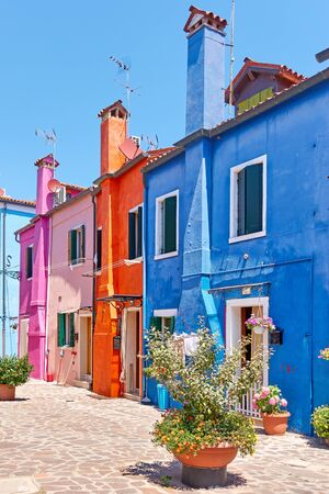 Street with colorful old houses with tall chineys in Burano island in Venice, Italy -- Italian cityscape Stock Photo