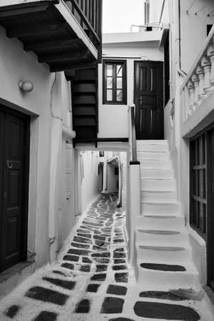 Perspective of narrow street in Mykonos (Chora) town, Greece. Black and white photography