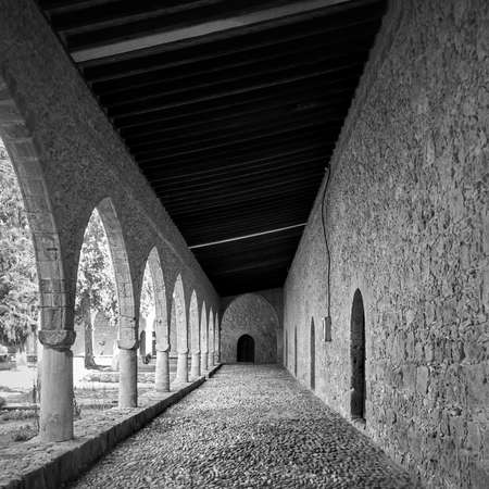 Perspective of covered gallery in ancient monastery in Ayia Napa, Cyprus. Black and white architectural photography Imagens