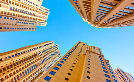 Multistory apartment buildings against the blue sky, Dubai, UAE.  Looking up
