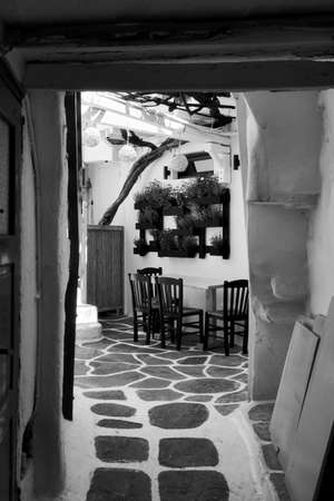 Patio in old small cafe in Mykonos island, Greece. Black and white photography