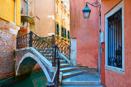 Canal with picturesque small bridge in Venice. Italy. Venetian cityscape, italian architecture