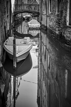 Small canal in Venice with bridge and moored boats, Italy. Black and white urban photography, venetian view