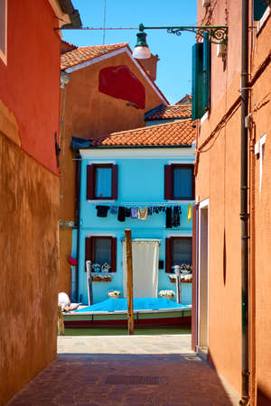 Small street by canal in Burano island in Venice, Italy.