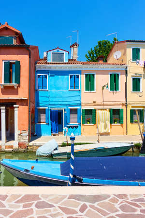 Colorful houses by canal in Burano in Venice, Italy. Venetian cityscape Standard-Bild