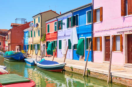 Colorful buildings by canal in Burano in Venice, Italy. Venetian cityscape, italian architecture
