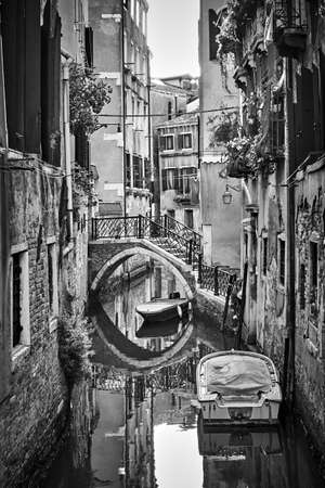 Side canal in Venice with small bridge and moored boats, Italy. Black and white urban photography, venetian cityscape