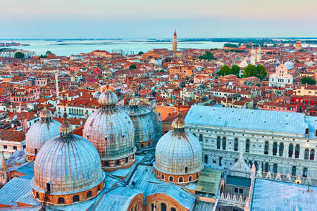 Panoramic view of Venice with domes of Cathedral Basilica of Saint Mark at dusk.