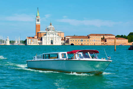Water taxi in Venice, Italy. Venetian view with San Giorgio Maggiore and motorboat, cityscape
