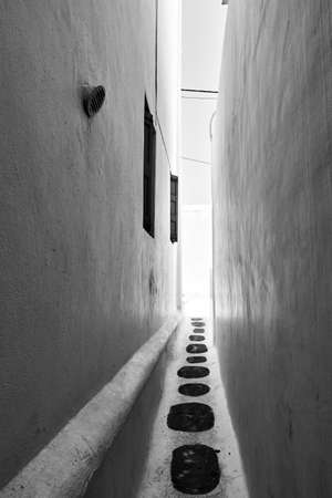 Very narrow alley in Chora town in Mykonos island, Greece,  Greek architecture, cityscape. Black and white photography