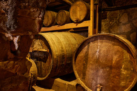 Wine barrels and casks with kegs on shelve in old wine-cellar
