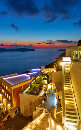Santorini island at night, Greece. View of Fira town at dusk with illuminated open-air bars