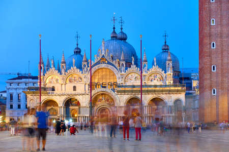 Cathedral Basilica of Saint Mark in Venice at dusk and people in motion blur in the square, Italy. Cityscape, landmark