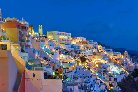Santorini at night, Greece. Landscape with Fira town at dusk, panoramic view