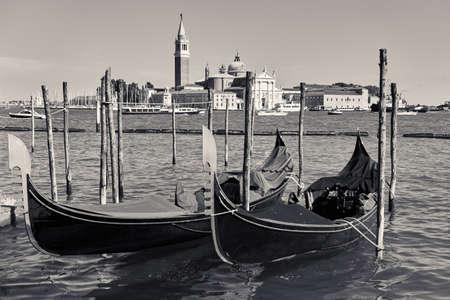 Venetian view with gondolas and San Giorgio Maggiore island, Venice, Italy. Landscape, black and white photography