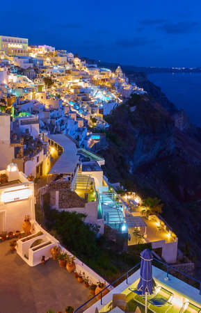 Brightly lit Fira town in Santorini island at dusk, Greece. Night landscape