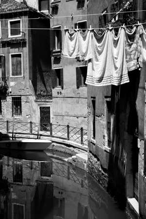 Canal in Venice with old houses and airing linen on the rope outdoors, Italy. Black and white photography, italian cityscape