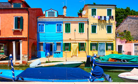 Cozy colorful houses and canal with boats in Burano Island in Venice, Italy. Cityscape, venetian view