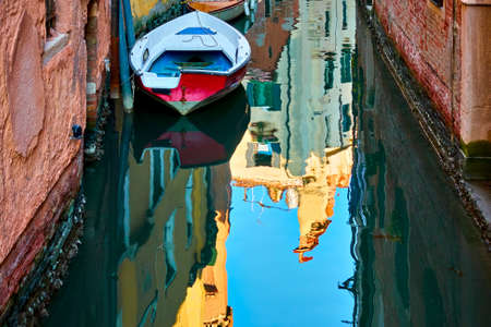 Narrow side canal with boat in Venice and water reflection on old houses, Italy. Venetian cityscape
