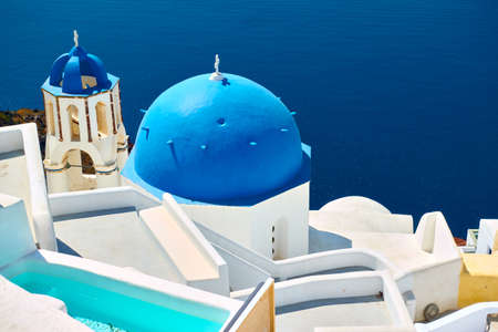 Santorini island in Greece. Sea and greek church with blue dome and bell tower