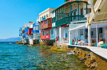 Mykonos, Greece - April 22, 2018: Tourists in cafes by the sea in Little Venice district in Mykonos (Chora) town