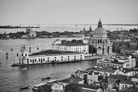 Venice with The Santa Maria della Salute church across the Grand Canal, Italy. Black and white panoramic venetian cityscape