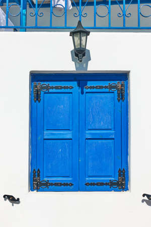 Greek whitewashed house with trditional blue shutters in Mykonos island, Greece. Architectural detail 版權商用圖片