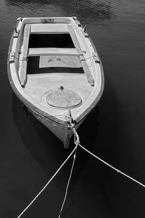 Moored old wooden oar boat. Black and white photography 版權商用圖片