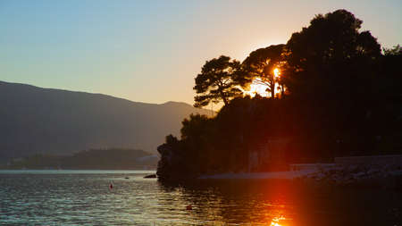 Sunset landscape with silhouettes of trees by the water. Nature of Montenegro, scenic panoramic view