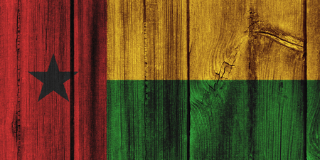 Guinea-Bissau  flag painted on wooden wall for background.