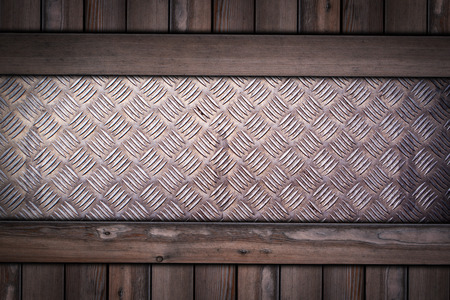 diamond pattern steel plate on wooden background.