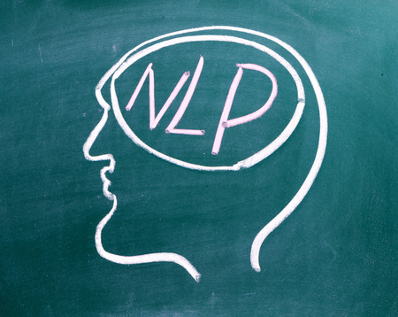 self   improvement: Drawing on a blackboard of a human head in profile with NLP on the brain. NLP is the acronym for Neuro-Linguistics Programming, often used in business and Psychotherapy for self improvement.  Stock Photo