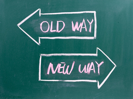 business change: Old Way, New Way written on a blackboard with arrows pointing in the direction of the past and the future. A concept for adapting to change, improvement and development for the self or the business  Stock Photo