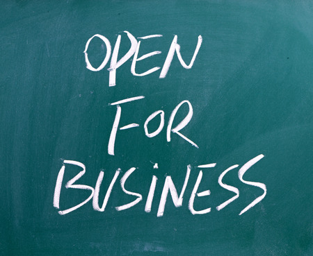 advertise with us: The phrase Open For Business hand written on a used blackboard Stock Photo