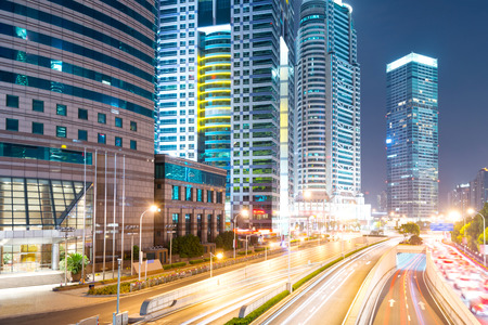 highway at night: the light trails on the modern building background in shanghai china. Stock Photo
