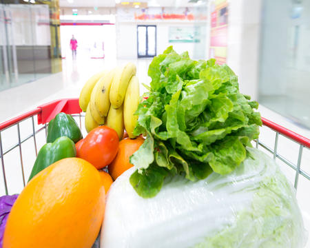 Supermarket interior, filled with the fruit and  Vegetables of the shopping cart.