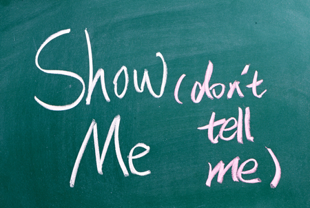 The phrase Show Me, Dont Tell Me written by hand on chalkboard. Often used in business but more so as a guide for novel and book writers