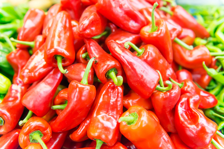 Display of locally grown red bell peppers for sale at local farmers market Stock Photo