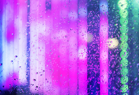 Wet window as the background of the night city