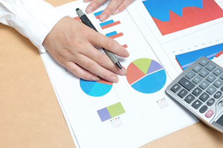 contaduria: woman hand with pen and business report. Accounting